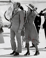 Wearing midi-dress with brown-and-white checks high neck, corsetted waist and a flaring skirt, Mrs. Margaret Trudeau walks with her husband. Prime Minister Pierre Trudeau, to meet the Queen at Vancouver International Airport.
