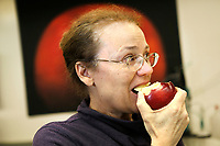 Dr. Katherine Evans, Associate Scientist and Associate Professor of Horticulture at WSU Tree Fruit Research and Extension Center, bites into a Cosmic Crisp apple in Wenatchee, WA on April 13, 2018. (Photo by Karen Ducey Photography)