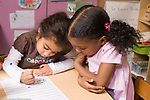 Education Preschool 3-4 year olds one girl watching another write her name on class sign-in sheet horizontal