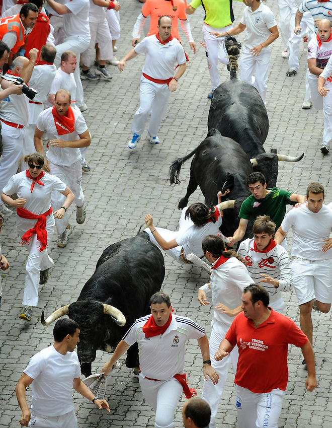 San Fermin, July 2012. Pamplona : Participants run with fighting bulls during a  San Fermin bull run in Pamplona. On each day of the San Fermin festival six bulls are released at 8:00 a.m. (0600 GMT) to run from their corral through the narrow, cobbled streets of the old navarre town over an 850-meter (yard) course. Ahead of them are the runners, who try to stay close to the bulls without falling over or being gored. Photo: Ander Gillenea.