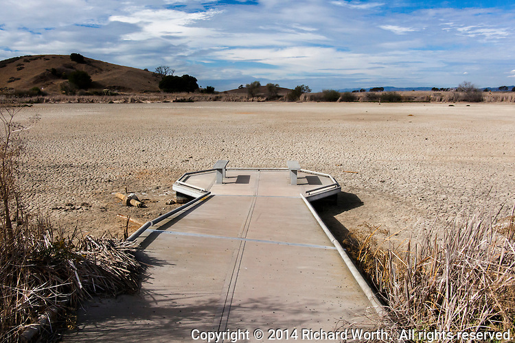 An observation deck, designed to float on the waters of the wetland, lies stranded on the dry cracked ground, a victim of the drought.