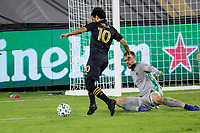 CARSON, CA - OCTOBER 28: Carlos Vela #10  of the Los Angeles FC attempts to move past goalkeeper Marko Maric #1 of the Houston Dynamo during a game between Houston Dynamo and Los Angeles FC at Banc of California Stadium on October 28, 2020 in Carson, California.