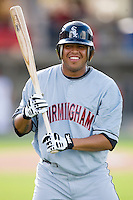 Clevelan Santeliz #47 of the Birmingham Barons messes around with a bat and batting helmet at Five County Stadium August 15, 2009 in Zebulon, North Carolina. (Photo by Brian Westerholt / Four Seam Images)