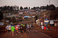 Athletes training with Kenyan elite marathoner Wilson Kipsang run through the town of  Iten, kenya on a morning run in April, 2012. Athletes from around the world have flocked to Kenya in advance of the Olympics, to be at the heart of the revolution in running that has seen world records and course records fall by minutes in recent years.