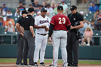 Somerset Patriots manager Julio Mosquera (25) meets with Altoona Curve manager Miguel Perez (29) and umpires Kelvis Velez, Steven Jaschinski, and Emil Jimenez prior to the game at TD Bank Ballpark on July 24, 2021, in Somerset NJ. (Brian Westerholt/Four Seam Images)