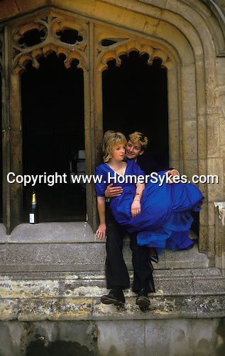 Oxford, Oxfordshire. 1985 <br /> Love Among the Ruins, sitting on the cloisters wall of the Quad, Emma Jenks in a royal blue taffeta ball gown contemplates, 'Where the quiet-coloured end of evening smiles'.  With her beau and a bottle of bubbly at Magdalen College Commem Ball.  <br /> <br /> <br /> <br /> <br /> The girl in the blue dress is Emma Jenks.