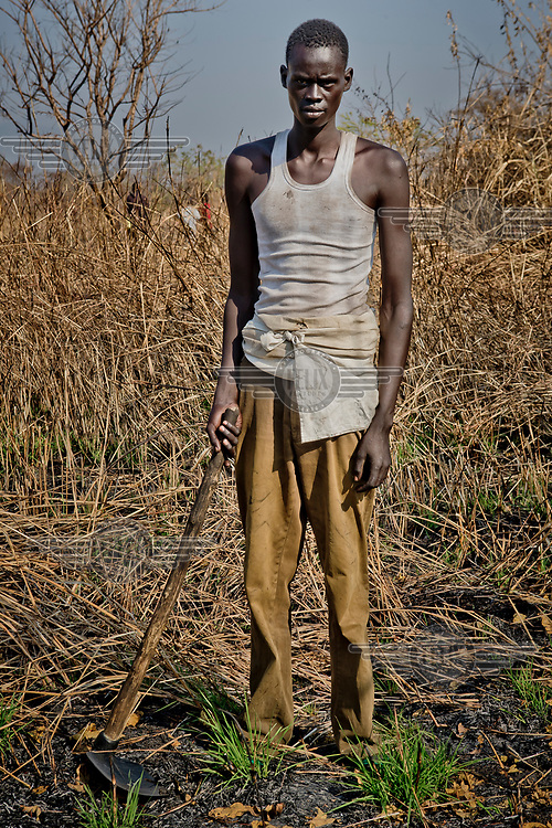 A South Sudanese refugee Michael Mayen Deng (20) on his allocated plot of land that at the Nyumanzi settlement that he must clear before building a shelter and eventually planting crops.