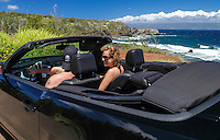 A couple in a black convertible explore the coastline of Maui.