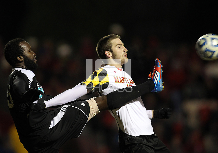 COLLEGE PARK, MD - NOVEMBER 25, 2012: Patrick Mullins (15) of the University of Maryland has the ball kicked away by Jhamie Hyde (5) of Coastal Carolina University during an NCAA championship third round match at Ludwig Field, in College Park, MD, on November 25. Maryland won 5-1.