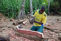 Nungwi, Zanzibar, Tanzania.  Dhow Construction.  Carpenter using an adze to shape an internal hull support.