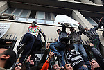 Protesters scaled the outside walls of the Interior Ministry, protecting it from demonstrators that filled the main avenue in downtown Tunis, Tunisia, Jan. 14, 2011. Several thousand people gathered outside the Ministry to protest and ask President Zine El Abidine Ben Ali to resign.