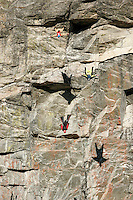 Three jumpers throw themselves head down from a mountain. In order to have control of their flight the jumpers must first gain as much speed as they can. The remote Eikesdal Valley has some spectacular mountains, well suited for BASE jumping. Norwegian BASE (Bridge, Antenna, Span, Earth - ie. parachute jumping from fixed objects) jumpers using wingsuits. First they drop vertically to gain speed, then the suits allow them fly over the sloping landscape. © Fredrik Naumann