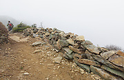Foggy conditions along the Appalachian Trail (Franconia Ridge Trail) in the New Hampshire White Mountains during the autumn months. The wall seen here is referred to as a Scree wall. These walls are built on the edge of trails to discourage hikers from going off trail. And building these small walls helps protect the fragile alpine habitat.