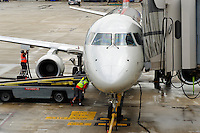 Commercial airplane being fueled and boarding passangers.