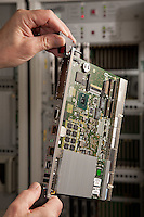 A man's hands hold a cicuit board ready to slot into a mainframe computer