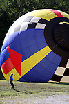 The top of a hot air balloon rising with the hot air and being directed by a safety man