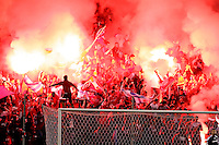The fans of Section 8 light flares to encourage the Fire.  The Chicago Fire defeated the New England Revolution 2-0 to win their playoff series at Toyota Park in Bridegview, IL on November 7, 2009.