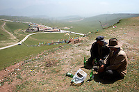 Two men drink beer on a hillside on the Qinghai-Tibetan Plateau, Qinghai Province. China. 2010