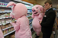 Moscow, Russia, 03/03/2011..A store guard watches as members of health campaign group Pigs Against check the sell-by dates and quality of food in a city centre supermarket while dressed in pig costumes.