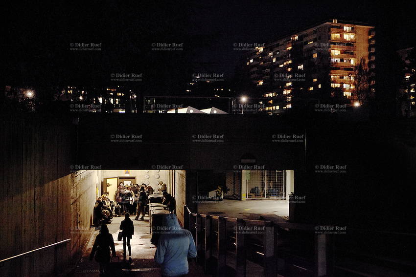 Switzerland. Geneva. A crowd of homeless people, both men and women, wait at nighttime to enter into the fallout shelter Richemont. The bunker was constructed as civil defense measures during the Cold War and is a unit of the Civil Protection. Switzerland is unique in having enough nuclear fallout shelters to accommodate its entire population. 11.02.2014 © 2014 Didier Ruef