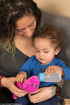 18 month old toddler boy with mother pretend play feeding soft dinosaur toy baby bottle