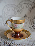 An antique demitasse cup and saucer sit on a lacey tablecloth.
