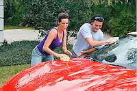 Young Couple in their 30s having fun washing car.