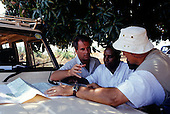 Gombe, Tanzania. Group of tourists on safari looking at a map on the bonnet of a four wheel drive vehicle.