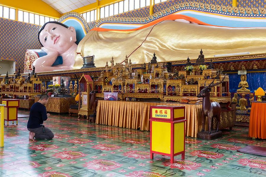 Worshiper Praying to Reclining Buddha in Wat Chayamangkalaram,  Temple.  George Town, Penang, Malaysia