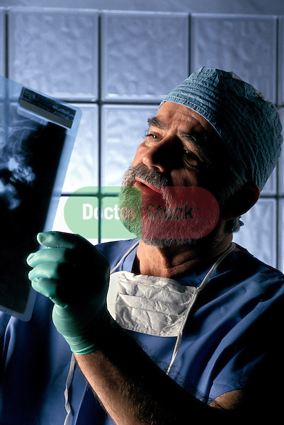 surgeon in scrubs looking at x-ray