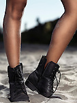Young woman legs in black leather boots standing in sand at the beach Image © MaximImages, License at https://www.maximimages.com