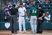 Chicago White Sox video technician Jack Larimer exchanges lineup cards with Greensboro Grasshoppers manager Kieran Mattison (24) as umpires Joe Belangia (left) and Dylan Bradley look on at Truist Stadium on August 13, 2021 in Winston-Salem, North Carolina. (Brian Westerholt/Four Seam Images)