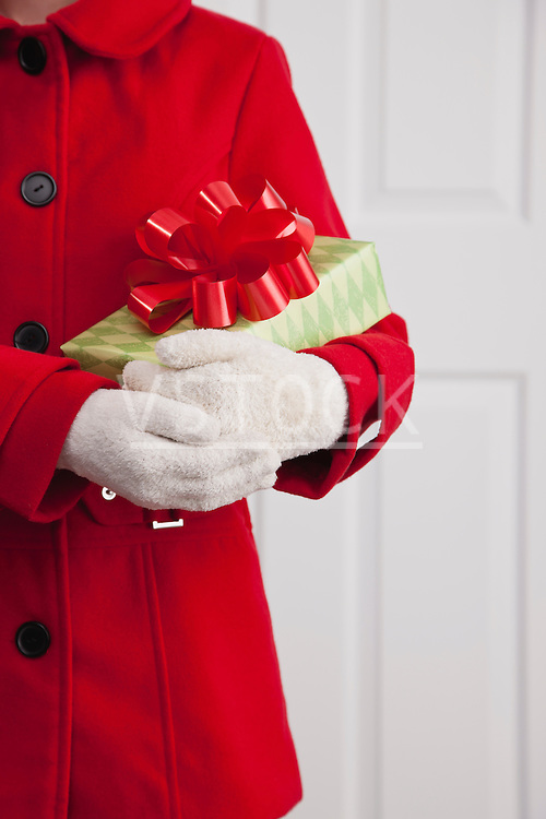 USA, Illinois, Metamora, Close up of girl (10-11) in red coat holding Christmas gift