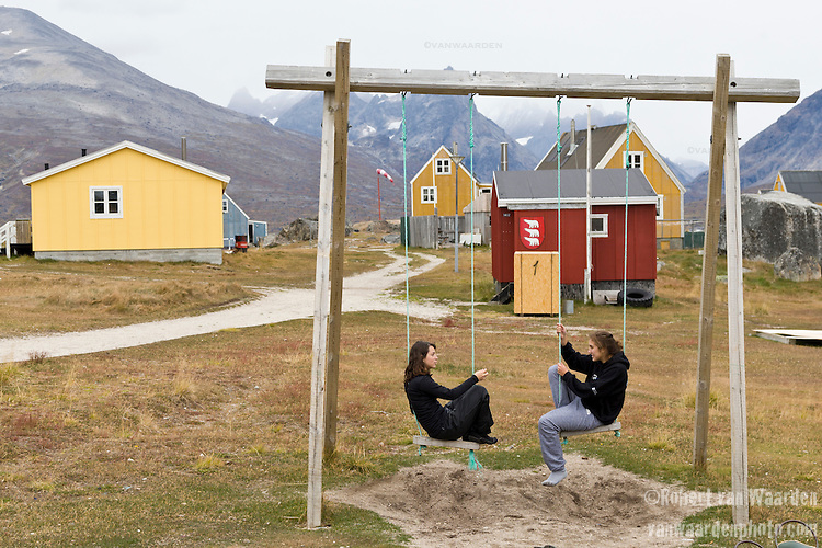 Two young women sit on the swings in the remote village of Tasiussaq, Greenland. The women are students on the Cape Farewell Youth Expedition that was organized by the British Council of Canada.