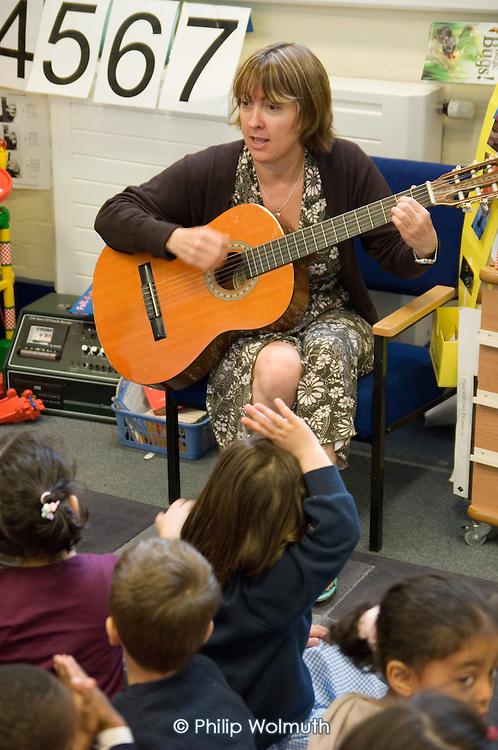 Teacher plays a guitar in a nursery class at Christ Church Bentinck Church of England Primary School, Westminster, London.