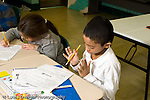 Education Elementary school Grade 2 boy and girl doing worksheets English language arts in class horizontal