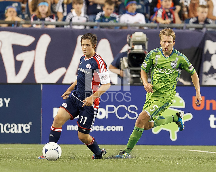 New England Revolution substitute midfielder Kelyn Rowe (11) dribbles as Seattle Sounders FC defender Adam Johansson (5) closes. In a Major League Soccer (MLS) match, the New England Revolution tied the Seattle Sounders FC, 2-2, at Gillette Stadium on June 30, 2012.