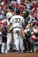 Michigan Wolverines pitching coach Chris Fetter talks with Karl Kauffmann (37) and Joe Donovan (0) on the mound during Game 1 of the NCAA College World Series against the Texas Tech Red Raiders on June 15, 2019 at TD Ameritrade Park in Omaha, Nebraska. Michigan defeated Texas Tech 5-3. (Andrew Woolley/Four Seam Images)