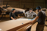 Aviation Maintenance Instructor Tom Mitchell instructs Aviation Maintenance students Robert Gibbs, left, and Junior Daniel, right, as they work on a wing after removing it from an aircraft in the hangar at UAA's Aviation Technology Complex on Merrill Field.