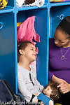 Education preschool 4 year olds female teacher talking with girl who is sitting in her cubby away from the rest of the children vertical