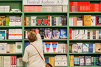 Hay on Wye, UK. Friday 27 May 2016<br /> A woman browses the books at the festival shop<br /> The 2016 Hay festival take place at Hay on Wye, Powys, Wales
