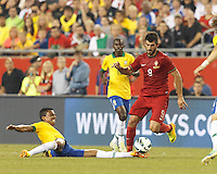 """Brazil midfielder Luiz Gustavo (17) slide tackles Portugal forward Nelson Oliveira (9). """"All ball."""" In an international friendly, Brazil (yellow/blue) defeated Portugal (red), 3-1, at Gillette Stadium on September 10, 2013."""