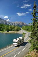 Vehicles travel by Long lake, adjacent to the Glenn Highway, Chugach mountains. Alaska