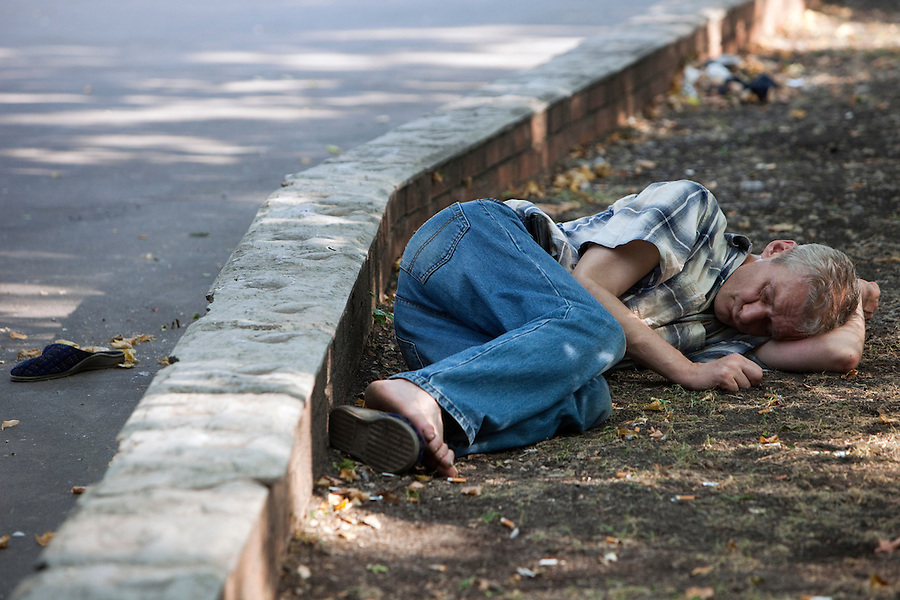 Moscow, Russia, 18/07/2010..A man collapses drunk in a park entrance after drinking alcohol outside in the current heatwave.
