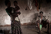 Villagers who fled their villagers from naxal affected areas were rehabilitated and are seen outside their hut in Pattagodam Salwa Judum camp in  Bhairamgarh, Chhattisgarh, India. Photo: Sanjit Das/Panos for The Times