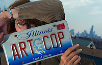 """4/6/04-Charles Osgood-Joy Neimanus, ending more than 30 years as photography professor at the School of the Art Institute of Chicago, displays her """"Art Cop"""" license plate which she will take with her to her new job and home in New Mexico. (Yes she was my teacher, but I didn't know she was the owner of the vehicle when I spotted the licence plate.) ..OUTSIDE TRIBUNE CO.- NO MAGS,  NO SALES, NO INTERNET, NO TV.. Tribune Photo by Charles Osgood 00224156A sidewalks"""
