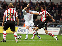Pictured: Gorka Pintado of Swansea (C) challenged by Jack Cork of Southampton (R)<br />