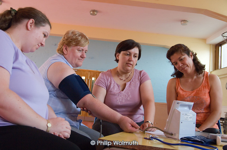 Elizabeth Welch checks the blood pressure of Noreen Parker at a healthy living session at Westbourne Park Family Centre.