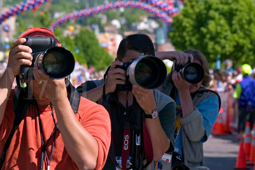 Photographers aiming camers with big lenses