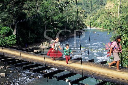 San Juan del Oro, Peru. Two Quechua women and a boy crossing a pedestrian suspension bridge over a river.